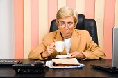 Senior Executive Reading News And Drinking Coffee