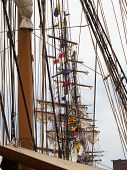 image of yardarm  - A view of the rigging and masts of several historic tall ships lined up one after the other - JPG