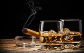 Whiskey drink with smoking cigar on wooden table