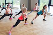 fitness, sport, training, people and lifestyle concept - group of women making lunge exercise in gym