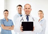 medicine, advertisement and teamwork concept - smiling male doctor with stethoscope showing tablet pc computer screen over group of medics