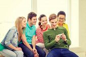 education, leisure and technology concept - five smiling students with digital camera at school