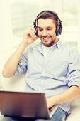 technology, home, music and lifestyle concept - smiling man with laptop and headphones at home