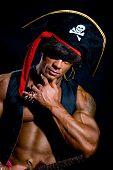 Close-up Portrait Muscular Pirate In The Studio On A Dark Background