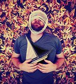 a man with a rope wrapped around his head laying in a pile of leaves holding a sailboat toned with a retro vintage instagram like filter effect