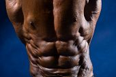 Close-up Of Abdominal Muscles Bodybuilder On A Blue Background