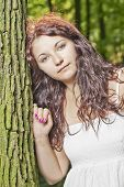 foto of wench  - Young girl standing near a tree trunk - JPG