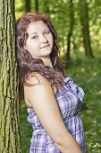picture of wench  - Young girl standing near a tree trunk - JPG