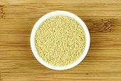 Raw Couscous In Bowl On Wooden Background