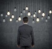 Businessman Looking To Light Bulbs