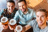 picture of casual wear  - Top view of three happy young men in casual wear toasting with beer while sitting in bar together - JPG