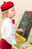 Cute Child Girl Drawing Chalk On Easel In Suit Of Artist In Preschool In Kindergarten