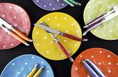 Dinner Party Table Setting With Red, Blue, Yellow, Orange, Green And Purple Bright Polka Dot Plates