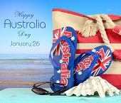 stock photo of shells  - Australian beach scene with Aussie sandals beach bag sunglasses and shell with view of blue ocean with Happy Australia Day sample text - JPG