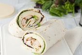 stock photo of sandwich wrap  - sandwich wrap or tortilla with leftover meat cheese and lettuce on white chopping board - JPG