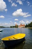 image of yellow castle  - A yellow boat with the castle of Trakai in the background Lithiania  - JPG