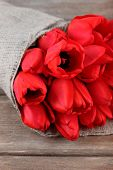 picture of sackcloth  - Bouquet of red tulips wrapped in sackcloth on wooden background - JPG