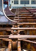 stock photo of shipyard  - Detail of the old and rusty machinery a disused shipyard ramp - JPG