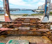 foto of shipyard  - Detail of the old and rusty machinery a disused shipyard ramp - JPG