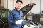 picture of garage  - Portrait of a smiling mechanic holding a wrench in his garage - JPG