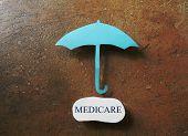 image of medicare  - A paper umbrella over a Medicare message - JPG