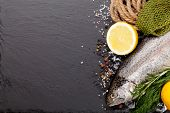 stock photo of trout fishing  - Fresh raw rainbow trout fish with spices and fishing equipment on black stone background - JPG