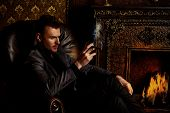 foto of cigar  - Elegant man in a suit with glass of beverage and cigar in vintage room - JPG