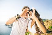 stock photo of love-making  - Couple in love making a heart shape with hands  - JPG