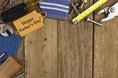 picture of tied  - Happy Fathers Day gift tag with corner border of tools and ties on a rustic wood background - JPG