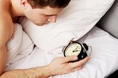 pic of early 20s  - Man lying on the bed with alarm clock - JPG