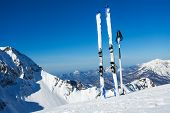 picture of caucus  - Ski put in snow with poles over the high mountain range panorama and piste - JPG
