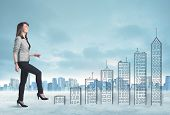 stock photo of climb up  - Business woman climbing up on hand drawn buildings in city concept - JPG