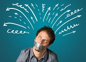 stock photo of taboo  - Young man with taped mouth and white drown lines and arrows around his head   - JPG