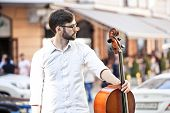 stock photo of cello  - The guy who plays the cello in the street in the summer - JPG