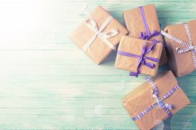 picture of text-box  - Wrapped boxes with presents in ray og light on turquoise painted wooden planks - JPG