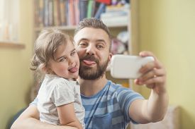 stock photo of selfie  - Young father with his cute little daughter taking selfie - JPG