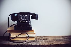 picture of traditional  - Black vintage rotary phone and books on rustic wooden table - JPG