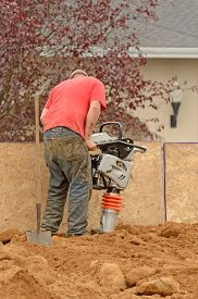 picture of vibration plate  - Commercial development building contractor working on building site installing a retaining wall - JPG