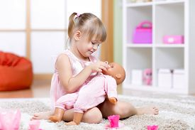picture of baby doll  - child girl playing with her baby - JPG