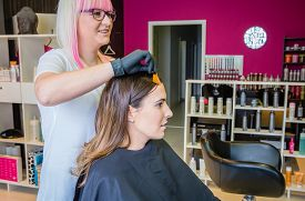 stock photo of hair dye  - Hairdresser showing hair dye sample to beautiful young woman before change her hair color  - JPG