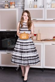 pic of ordinary woman  - Happy ordinary woman with pan at her kitchen - JPG