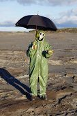 stock photo of scoria  - The person in protective clothes with an umbrella waits a radioactive rain - JPG