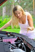 Joven, comprobación de nivel de aceite en el coche