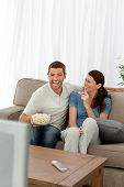 Cheerful Couple Eating Pop Corn While Watching A Comic Movie