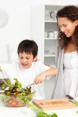 Cute Boy Mixing A Salad With His Mother In The Kitchen