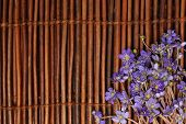 Violet Flowers On A Brown Wooden Mat. Background