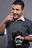 Funny man with a digital camera and finger in his nose