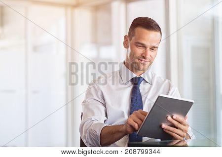 Smiling businessman using digital tablet