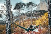 Back view of traveler man hiking and relaxing in hammock in autumn woods and looking at mountain hil poster
