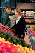 stock photo of grocery store  - A woman buying groceries in a supermarket receiving help from a shop assistant - JPG